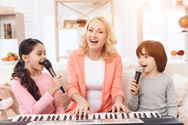 Avó com crianças tocando piano cantando em casa