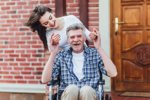 Avô com deficiência alegre em cadeira de rodas, dando as boas-vindas a sua neta feliz perto do lar de idosos