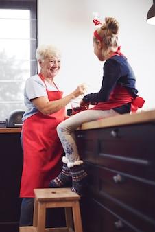 Avó com menina cozinhando e curtindo