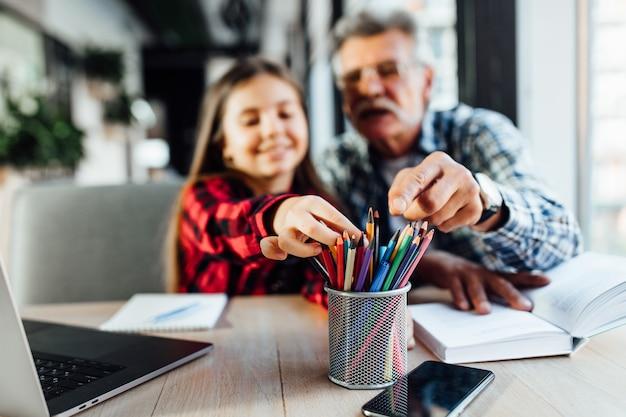Avô com neta desenhando em um café