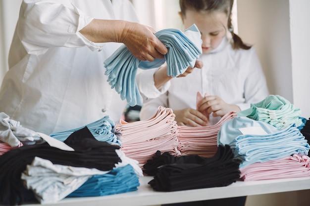 Avó com neta medir o tecido para costura
