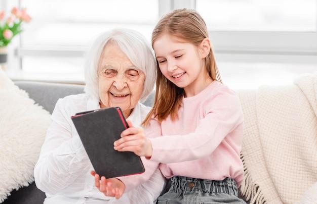Avó com neta usando tablet
