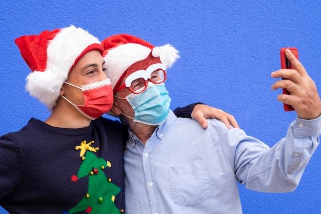 Avô com neto adolescente sorri usando telefone inteligente para tirar uma selfie, usando máscara cirúrgica devido a coronavírus e chapéus de papai noel. conceito de família, amizade e diversão