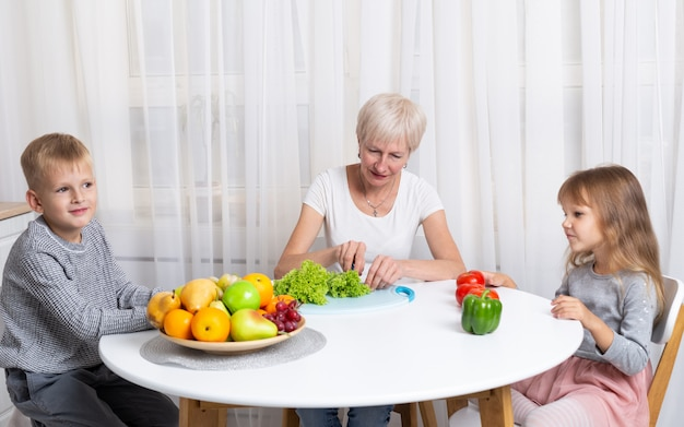 Avó com neto e neta preparam alimentos saudáveis na cozinha. família preparando uma salada juntos