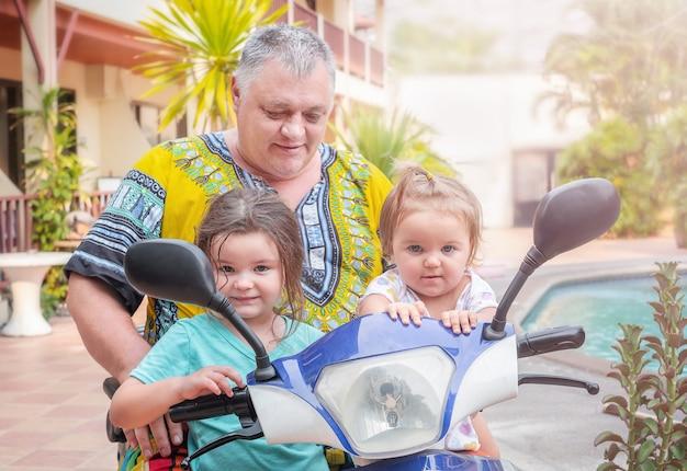 Avô com netos em um retrato de moto elétrica