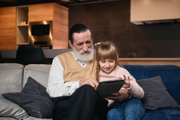 Avô com sua neta usando tablet em casa