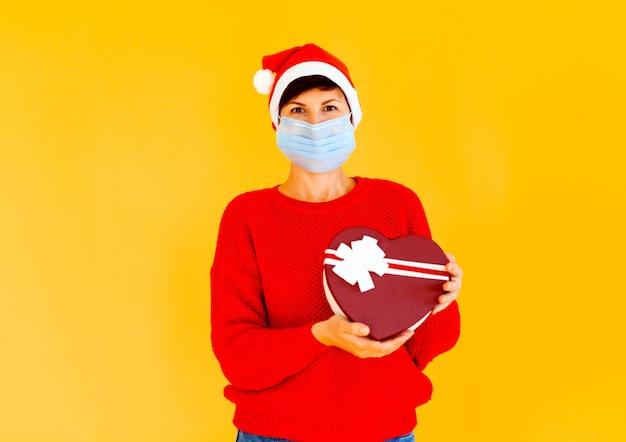 Avó com um boné de gnomo e uma máscara médica segura um presente de ano novo. em um estúdio fotográfico de fundo preto. feliz ano novo de 2021.