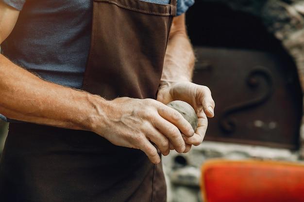 Avó com um neto faz jarros em cerâmica
