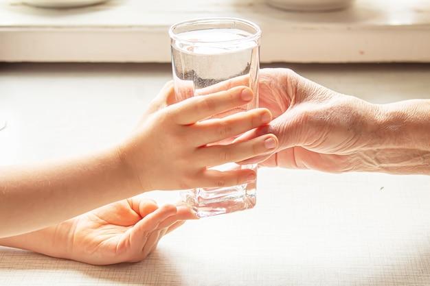 Avó dando um copo de água limpa para uma criança. foco seletivo. natureza.
