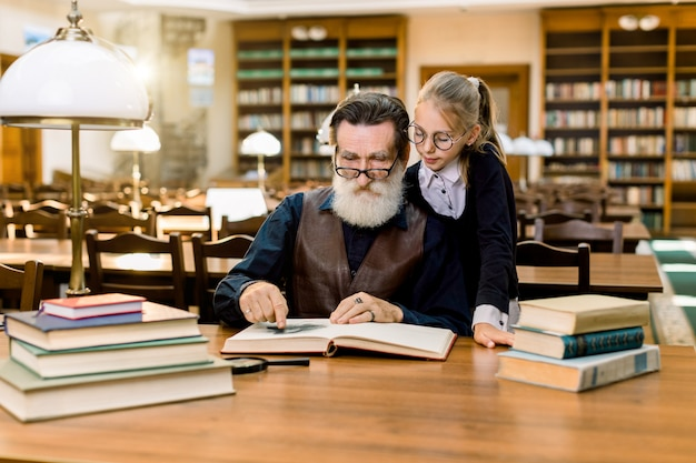 Avô de homem idoso e sua neta lendo livro emocionante juntos na biblioteca antiga vintage