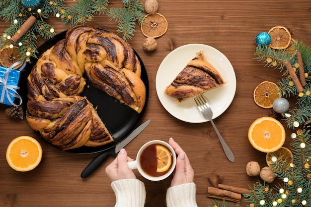 Avó de natal de chocolate na forma de uma coroa de flores com calda de laranja em um prato cortado em pedaços. decorações de natal em uma mesa de madeira.