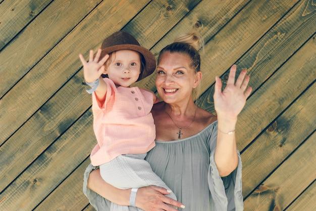 Avó de retrato de emoção e sua neta em roupas de musselina de estilo rural em madeira backgrou