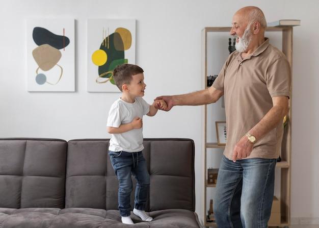 Avô de tiro médio brincando com uma criança
