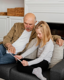 Avô de tiro médio e menina com tablet