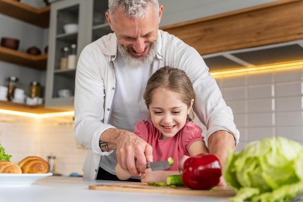 Avô de tiro médio e menina na cozinha