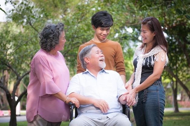 Avô deficiente alegre na cadeira de rodas que dá boas-vindas a sua família feliz.