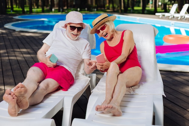 Avó e avô com óculos de sol brilhantes, deitados em espreguiçadeiras tomando banho de sol