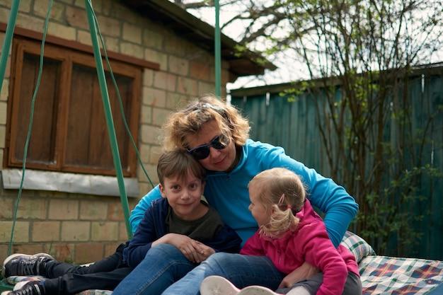 Avó e dois netos se divertindo em um balanço, neto e neta amam a avó. outdors relaxantes na casa de campo da vovó.