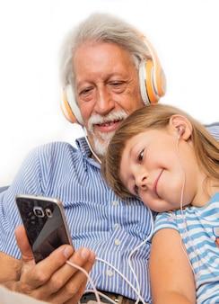 Avô e filha ouvem música com fone de ouvido