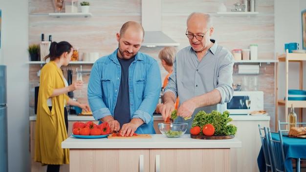 Avô e filho na sala de jantar preparando uma salada fresca. um homem de meia-idade e um idoso mais velho se divertem trabalhando juntos preparando o jantar em uma cozinha moderna, enquanto as mulheres conversam ao fundo.