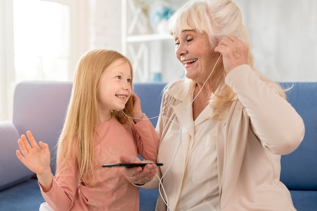 Avó e garota ouvindo música em casa
