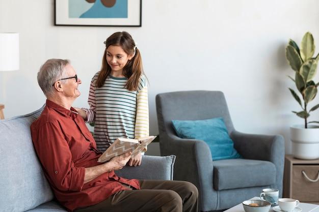 Avô e menina com livro