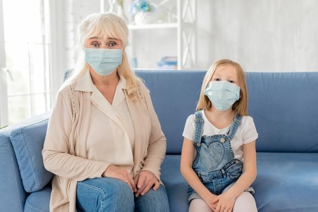 Avó e menina com máscara no sofá
