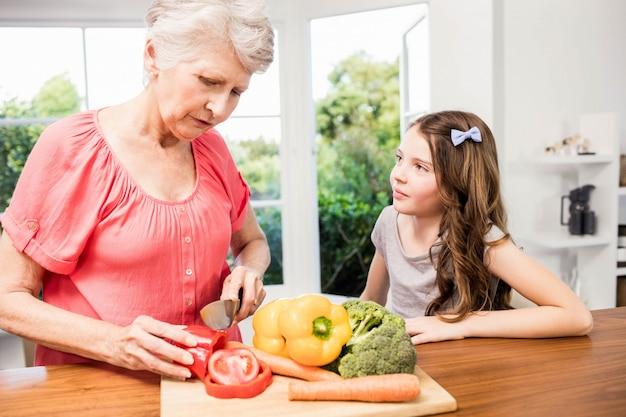 Avó e neta cortando legumes na cozinha