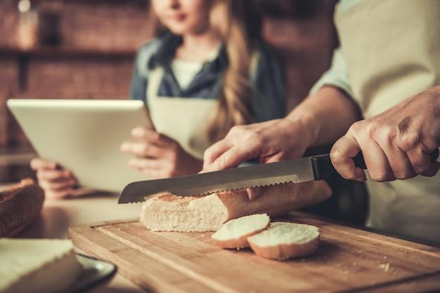 Avó e neta cortando pão.