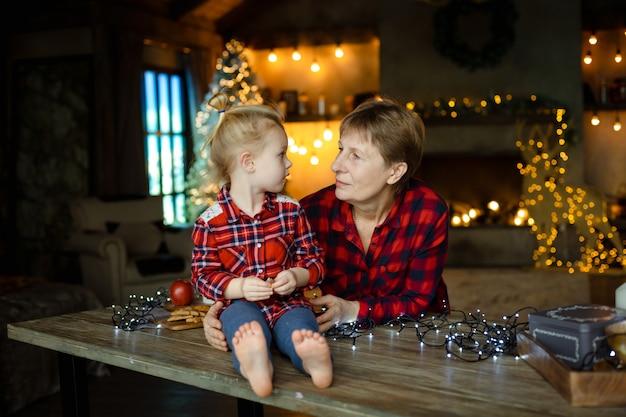 Avó e neta em um aconchegante, decorado para casa de natal, olhando um ao outro.
