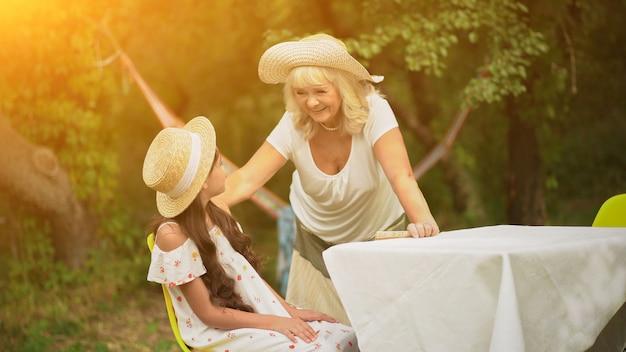 Avó e neta estão à mesa no jardim