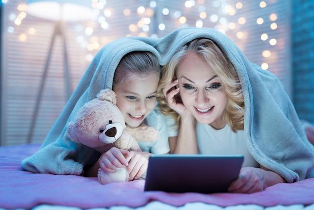 Avó e neta estão assistindo filme no tablet.