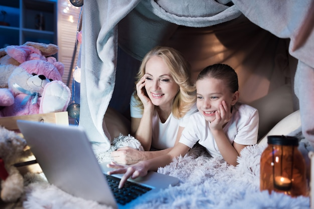 Avó e neta estão conversando com a família no laptop em casa cobertor à noite em casa.