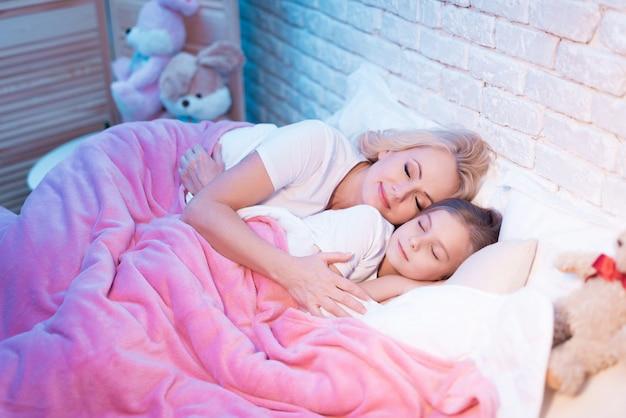 Avó e neta estão deitada na cama à noite.
