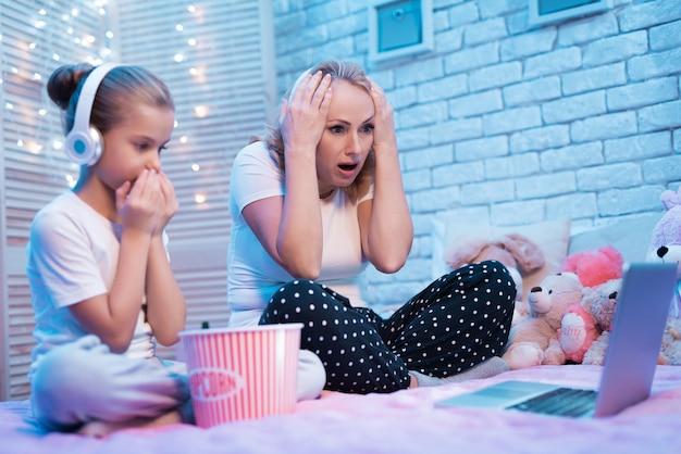 Avó e neta ficam chocadas assistindo filme à noite em casa.