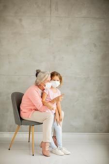 Avó e neta fofa usando máscaras respiratórias