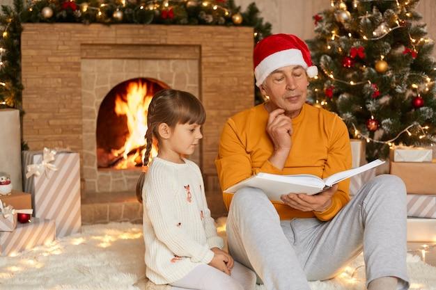 Avô e neta lendo contra a lareira e a árvore de natal na sala de estar, o homem sênior segura o livro e olha para as páginas com expressão pensativa, o homem e a menina usam casualmente.