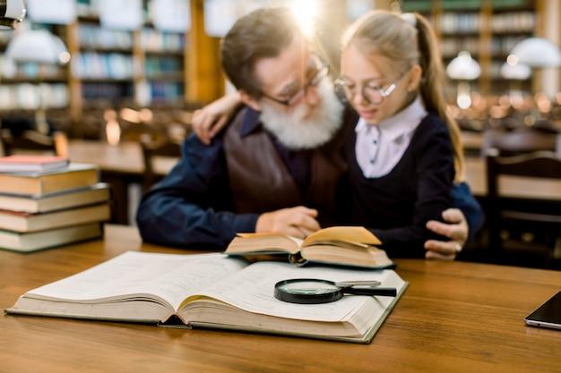 Avô e neta lendo um livro na antiga biblioteca da cidade vintage