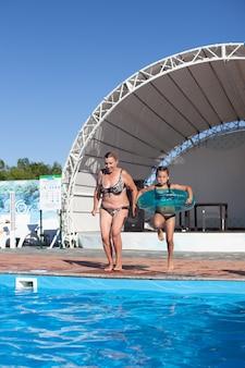 Avó e neta na piscina alegres se divertindo, avó e neta alegremente ...