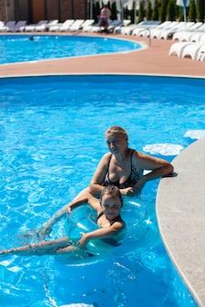 Avó e neta na piscina uma avó feliz e uma neta sorridente em um infl ...
