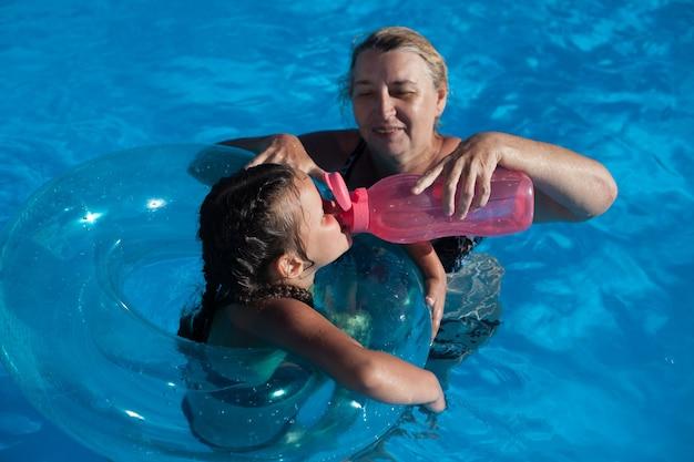 Avó e neta na piscina uma jovem avó dá a sua neta água de um r ...