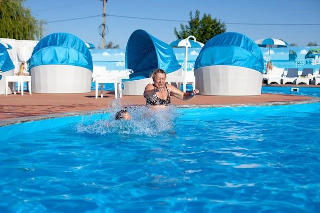 Avó e neta na piscina uma jovem avó e neta alegremente pulam na piscina.