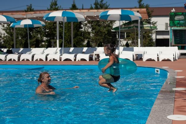 Avó e neta na piscina uma neta em um círculo inflável salta da borda ...