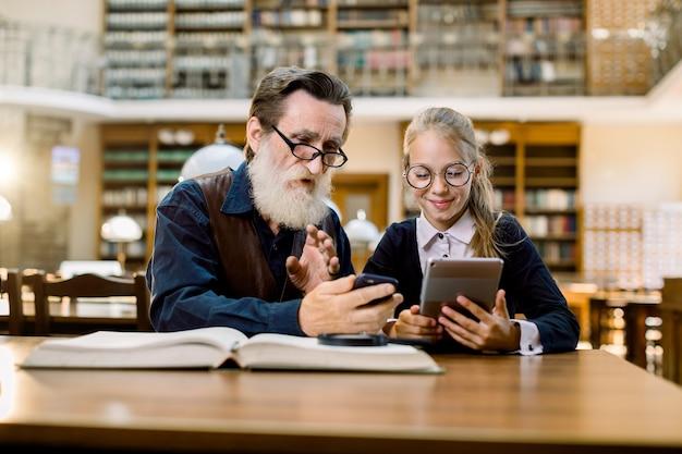 Avô e neta, professor e aluno, sentados juntos à mesa usando tablet digital, smartphone e livros.