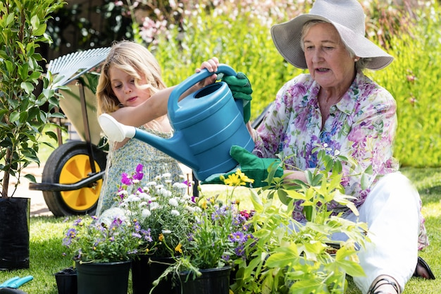 Avó e neta regando as plantas no jardim