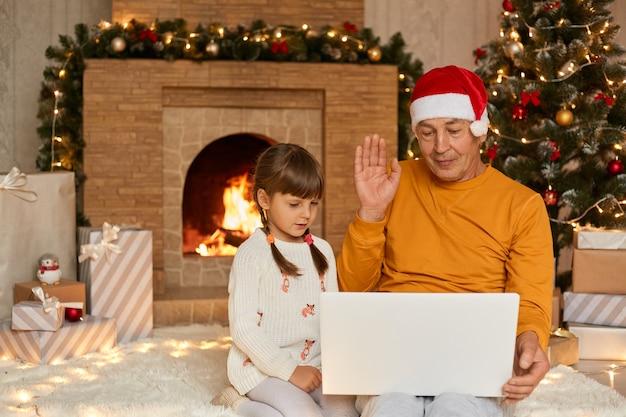 Avô e neta tendo um vídeo no notebook, acenando com as mãos para a câmera, parabenizando alguém com vésperas de ano novo, vestindo casualmente, sentado perto da lareira e a árvore de natal.