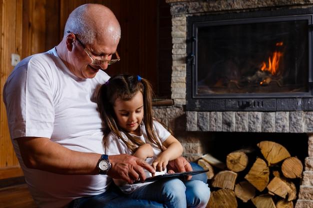 Avô e neta usando tablet de uma casa perto da lareira