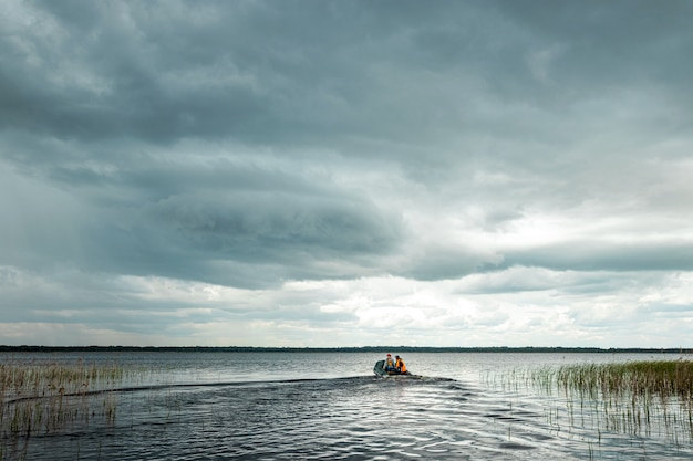 Avô e neto andam de barco a motor no lago.