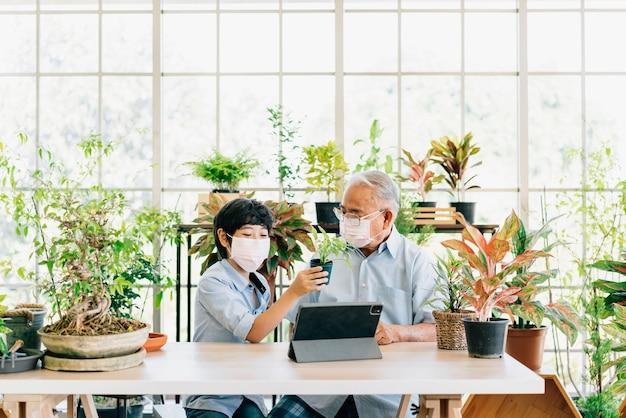 Avô e neto aposentados asiáticos usando uma máscara facial e vivem para vender plantas em um tablet se divertindo.