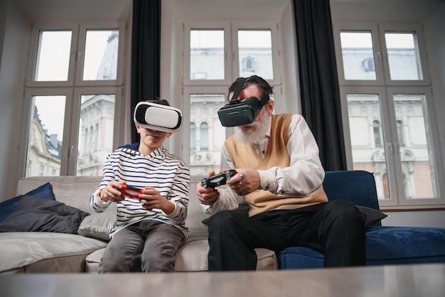 Avô e neto estão jogando videogame no computador à mesa à noite em casa.